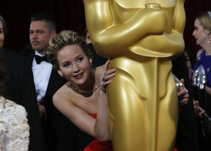 """Jennifer Lawrence, best supporting actress nominee for her role in the film """"American Hustle"""", peeks around an Oscar statue on the red carpet as actor Brad Pitt (L) looks on at the 86th Academy Awards in Hollywood, California March 2, 2014. REUTERS/Adrees Latif (UNITED STATES  - Tags: ENTERTAINMENT)(OSCARS-ARRIVALS)"""