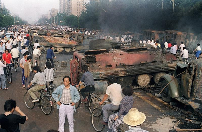 Beijing residents gather around the smoking remains of over 20 armoured personnel carriers -- burnt by demonstrators during clashes with soldiers near Tiananmen Square -- on June 4, 1989 (AFP Photo/Manny CENETA)