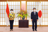 Japan's Foreign Minister Toshimitsu Motegi, right, and Indonesian Foreign Minister Retno Marsudi, wearing protective face masks, pose for a photograph prior to the Japan Indonesia Foreign Ministers meeting in Tokyo on Monday, March 29, 2021. Indonesian Foreign Minister Retno Marsudi and Defense Minister Prabowo Subianto are in Japan from March 28-30, 2021. (David Mareuil/Pool Photo via AP)