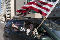 A Biden supporter cheers while driving past a Trump rally protesting the election results after Democrat Joe Biden was declared the winner Saturday, Nov. 7, 2020, at the State Capitol in Lansing, Mich. Biden defeated President Donald Trump to become the 46th president of the United States on Saturday, positioning himself to lead a nation gripped by the historic pandemic and a confluence of economic and social turmoil. (AP Photo/David Goldman)