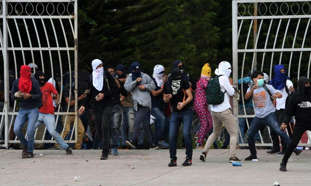 """<span class=""""element-image__caption"""">Students clash with riot police during a protest against the reelection of President Juan Orlando Hernández, in Tegucigalpa on 5 February 2018. </span> <span class=""""element-image__credit"""">Photograph: Orlando Sierra/AFP/Getty Images</span>"""