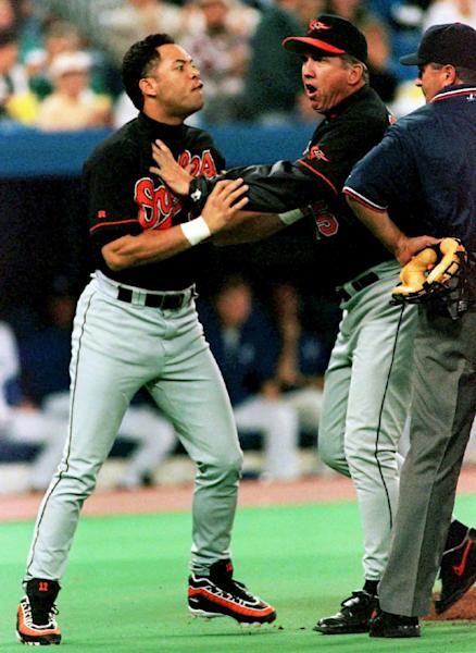 FILE - In this Sept. 27, 1996, file photo, Baltimore Orioles second baseman Roberto Alomar, left, is held back by manager Davey Johnson, center, as he takes a run at home plate umpire John Hirshbeck after being ejected from the game during first inning baseball action against the Toronto Blue Jays in Toronto. (AP Photo/Moe Doiron, File)