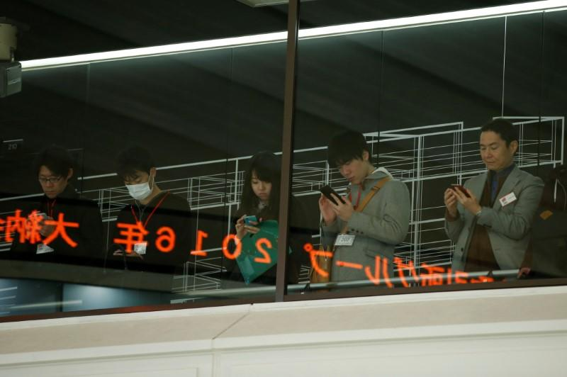 Visitors use their mobile phones before a ceremony marking the end of trading in 2016 at TSE in Tokyo