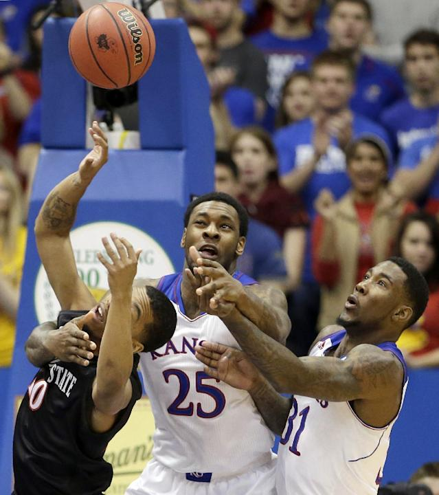 Kansas' Tarik Black (25) and Jamari Traylor (31) battle San Diego State's Aqeel Quinn for a rebound during the first half of an NCAA college basketball game Sunday, Jan. 5, 2014, in Lawrence, Kan. (AP Photo/Charlie Riedel)