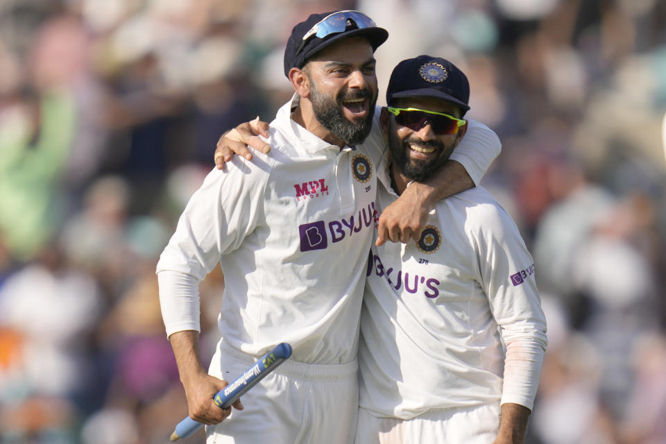 India's Virat Kohli, left, and India's KL Rahul smile as they leave the pitch after India beat England by 157 runs on day five of the fourth Test match at The Oval cricket ground in London, Monday, Sept. 6, 2021. (AP Photo/Kirsty Wigglesworth)