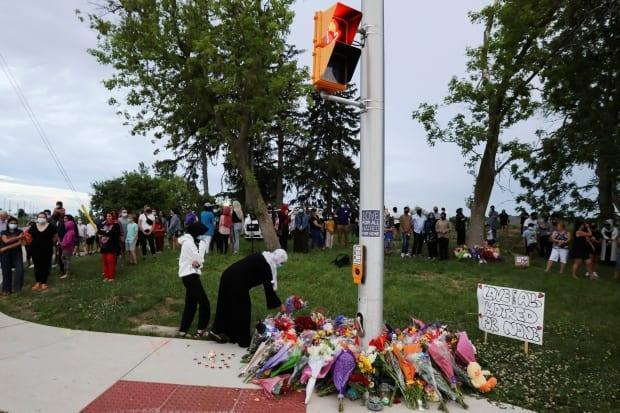 People are seen at a makeshift memorial at the spot where the four family members were killed in what police say was a deliberately targeted anti-Islamic attack, in London, Ont.  (Carlos Osorio/Reuters - image credit)
