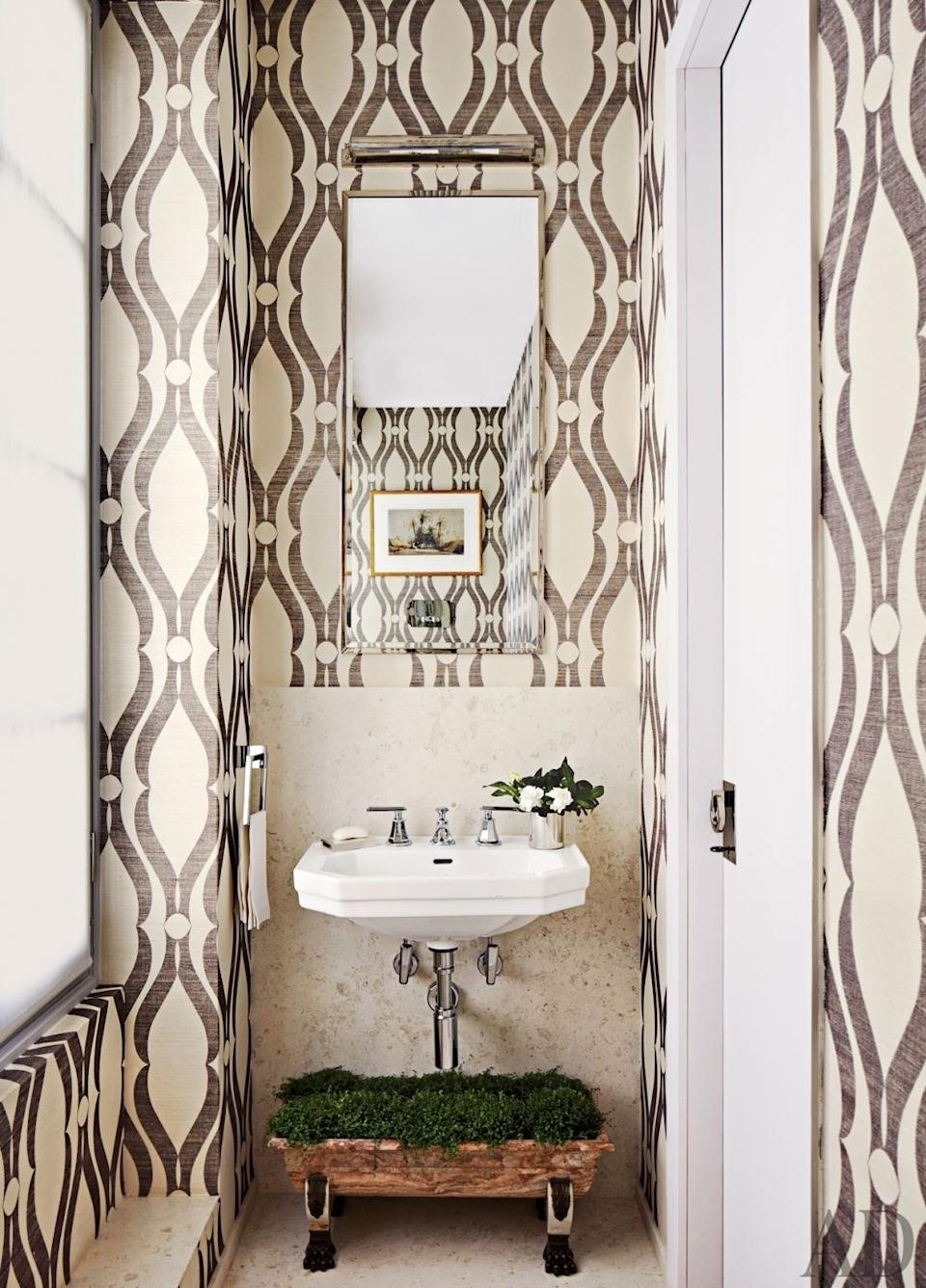 The powder room of a house in Monte Carlo features Dornbracht fittings and Phillip Jeffries wallpaper.