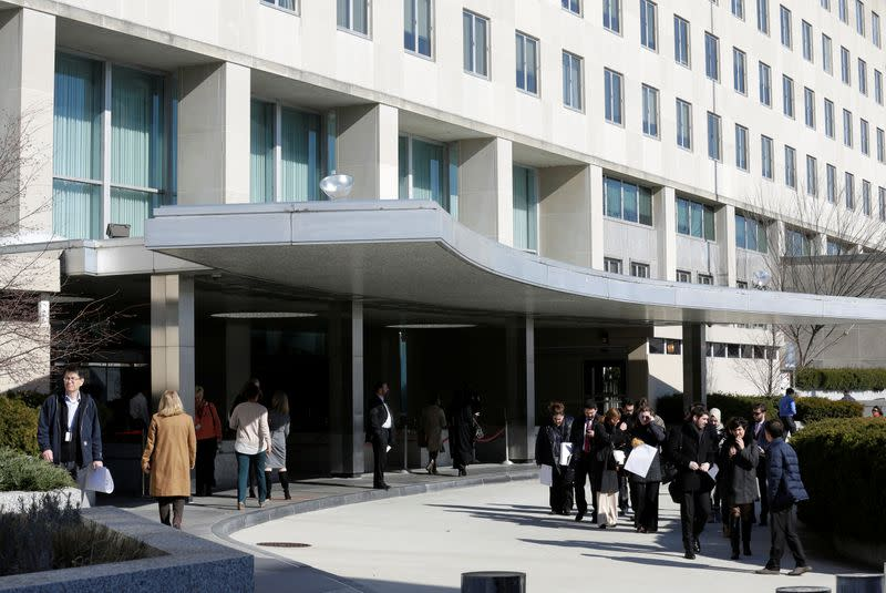 People enter and leave State Department Building in Washington