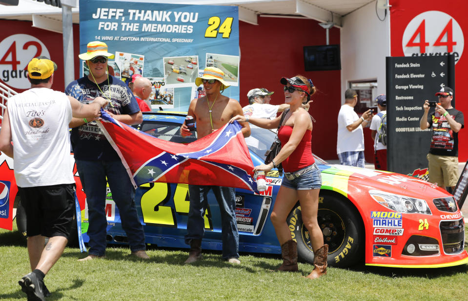 FILE - In this July 5, 2015, file photo, race fans make a photo with a Confederate flag in the Fan Zone before a NASCAR Sprint Cup series auto race at Daytona International Speedway. in Daytona Beach, Fla. A predominantly white sport with deep Southern roots and a longtime embrace of Confederate symbols, NASCAR was forced last summer to face its own checkered racial history during the country's social unrest. (AP Photo/Terry Renna, File)