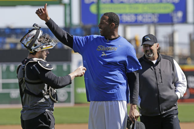 Retired NBA All-Star Tracy McGrady, center, gives a thumbs up as Sugar Land Skeeters catcher Koby Clemens, left, tries to hand him the ball and manager Gary Gaetti smiles at the Skeeters' baseball stadium Wednesday, Feb. 12, 2014, in Sugar Land, Texas. McGrady hopes to try out as a pitcher for the independent Atlantic League Skeeters. (AP Photo/Pat Sullivan)