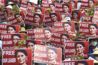 Protesters hold up placard with images of ousted leader Aung San Suu Kyi during an anti-coup protest in Mandalay, Myanmar, Sunday, Feb. 21, 2021. Police in Myanmar shot dead a few anti-coup protesters and injured several others on Saturday, as security forces increased pressure on popular revolt against the military takeover. (AP Photo)