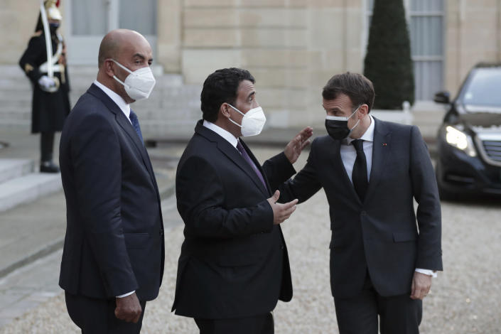 French President Emmanuel Macron, right, talks with Mohammad Younes Menfi, president of Libya's Presidential Council, center, and Musa al-Koni, vice-president of Libya's Presidential Council, left, at the end of a meeting, at the Elysee Palace, in Paris, Tuesday, March 23, 2021. Macron said France will reopen its embassy in Libya's capital Tripoli on Monday as a gesture of support for the new interim government. (AP Photo/Thibault Camus)
