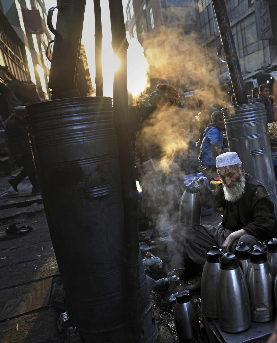 Afghan tea seller Farooq Shah, center, fills kettles with tea for customers at a market place in Kabul, Afghanistan, Wednesday, Dec. 4, 2019. (AP Photo/Altaf Qadri)