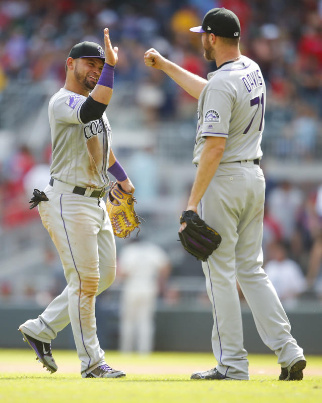 Colorado Rockies left fielder Gerardo Parra, left, celebrate a win with relief pitcher Wade Davis (71) at the conclusion of a baseball game against the Atlanta Braves, Sunday, Aug. 19, 2018, in Atlanta. (AP Photo/Todd Kirkland)