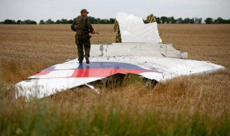 An armed pro-Russian separatist stands on part of the wreckage of the Malaysia Airlines Boeing 777 plane after it crashed near the settlement of Grabovo in the Donetsk region, July 17, 2014. The Dutch are due to announce on Wednesday 28 September the long-awaited results of an investigation with Australia, Malaysia, Belgium and Ukraine into the July 17, 2014 downing of the flight. REUTERS/Maxim Zmeyev/File Photo