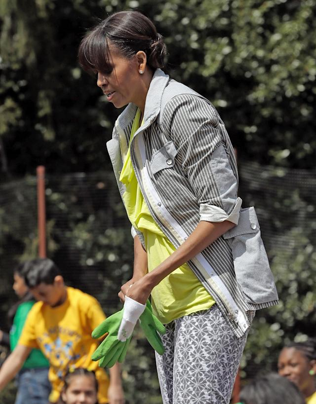 "WASHINGTON, DC - APRIL 04: U.S. first lady Michelle Obama pulls on a pair of work gloves while planting the White House Kitchen Garden on the South Lawn of the White House April 4, 2013 in Washington, DC. For the fifth time, the first lady invited students from ""schools that have made exceptional improvements to school lunches"" from Florida, Massachusetts, Tennessee and Vermont to help her plant the garden. (Photo by Win McNamee/Getty Images)"