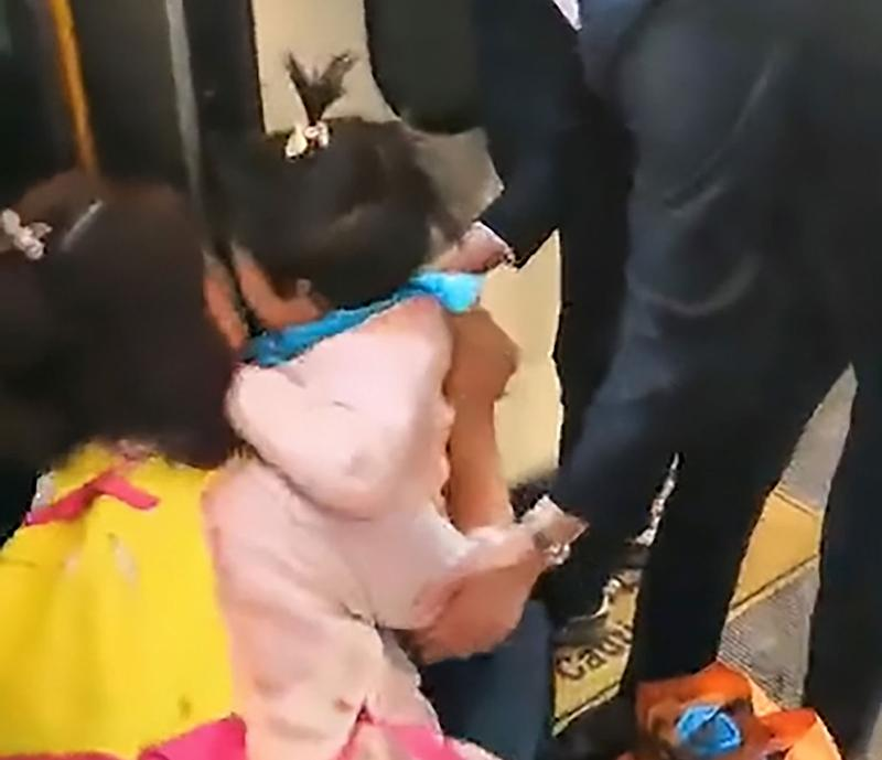 A little girl has fallen through a gap at a train platform at Beijing Railway Station while her mum was distracted by her phone. Source: AsiaWire/ Australscope