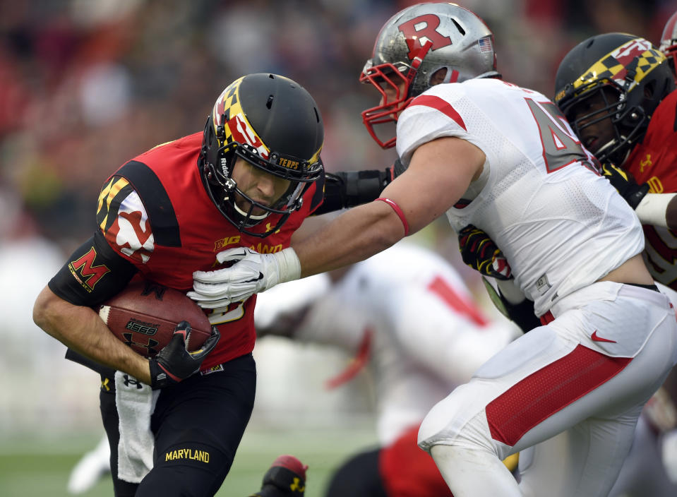 Maryland quarterback C.J. Brown, left, runs with the ball against Rutgers linebacker Kevin Snyder, right, during the first half of an NCAA college football game, Saturday, Nov. 29, 2014, in College Park, Md. (AP Photo/Nick Wass)