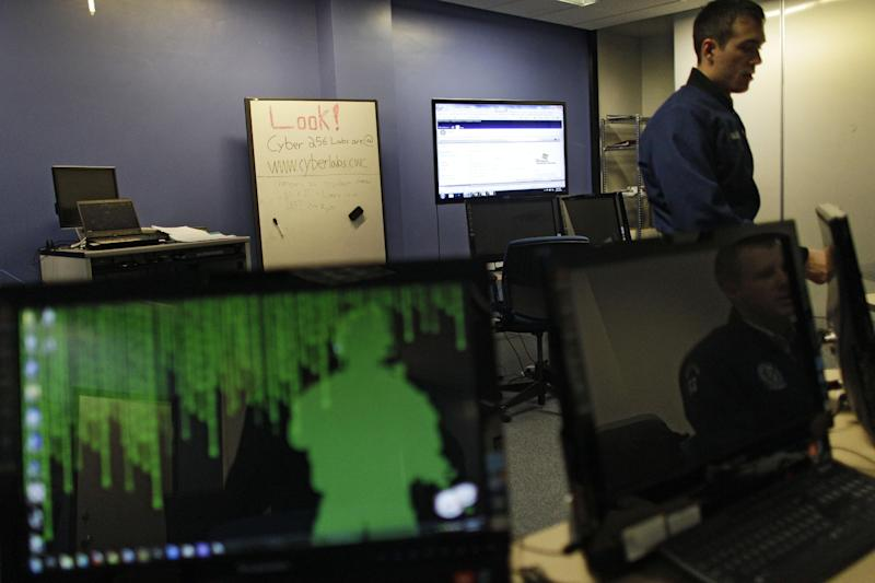 In this Feb. 20, 2013 photo, a cadet walks past multiple computer displays inside a classroom at the Center for Cyberspace Research, where cyber warfare is taught, at the U.S. Air Force Academy, in Colorado Springs, Colo. The U.S. service academies are ramping up efforts to groom a new breed of cyberspace warriors to confront increasing threats to the nation's military and civilian computer networks that control everything from electrical power grids to the banking system. (AP Photo/Brennan Linsley)