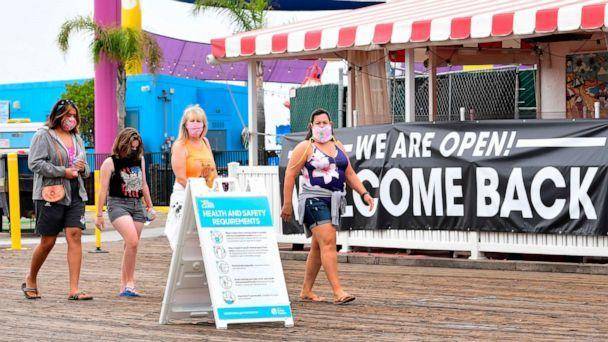 PHOTO: People wearing face masks walk past a health and safety guidelines board and an open restaurant on the pier in Santa Monica, California, on June 26, 2020. (Frederic J. Brown/AFP via Getty Images, FILE)