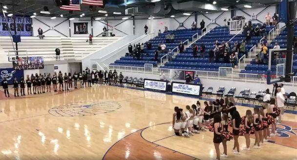 PHOTO: Players from Norman High School girls' basketball team in Norman, Okla., take a knee during the national anthem before a state quarterfinals game on March 11, 2021. (Clay Horning/The Transcript)