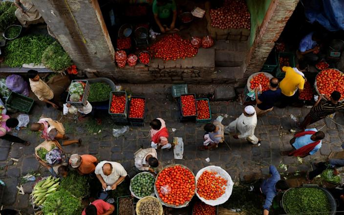 People shop at a crowded wholesale vegetable market after authorities eased coronavirus restrictions, following a drop in Covid-19 cases, in the old quarters of Delhi - Adnan Abidi/Reuters