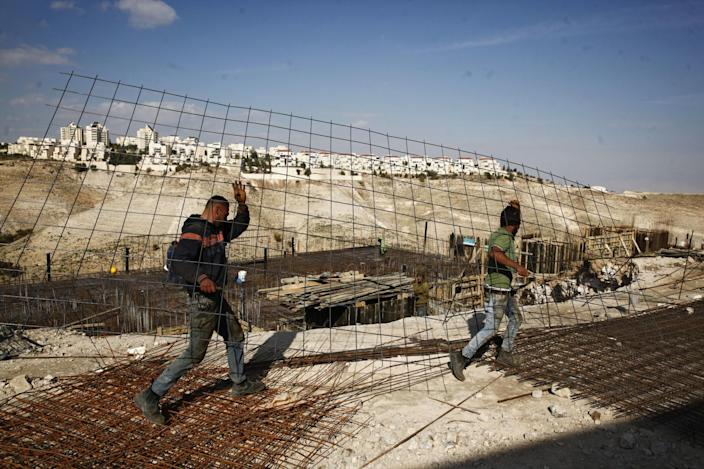 Workers carry material at a construction site in the West Bank settlement of Maale Adumim. (Photo: Mahmoud Illean/AP)
