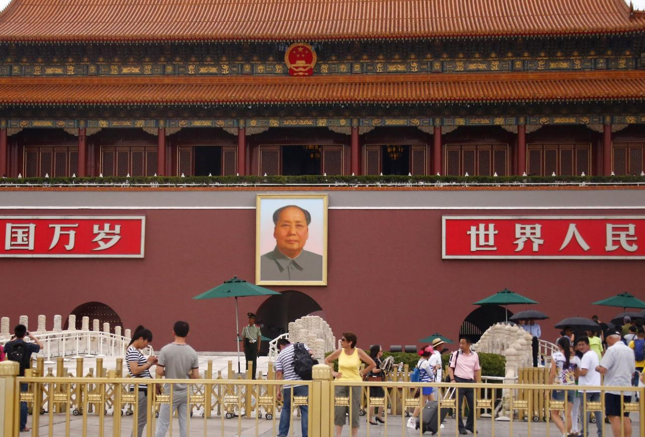 Visitors stand near paramilitary policemen standing guard in front of a giant portrait of China's late Chairman Mao Zedong and Tiananmen Gate in Beijing June 4, 2014. China deployed its vast security apparatus on Wednesday to snuff out commemoration of the suppression of pro-democracy protests around Tiananmen Square 25 years ago, flooding the streets with police as censors scrubbed the Internet clean of any mention of the crackdown. REUTERS/Petar Kujundzic (CHINA - Tags: MILITARY ANNIVERSARY POLITICS SOCIETY)
