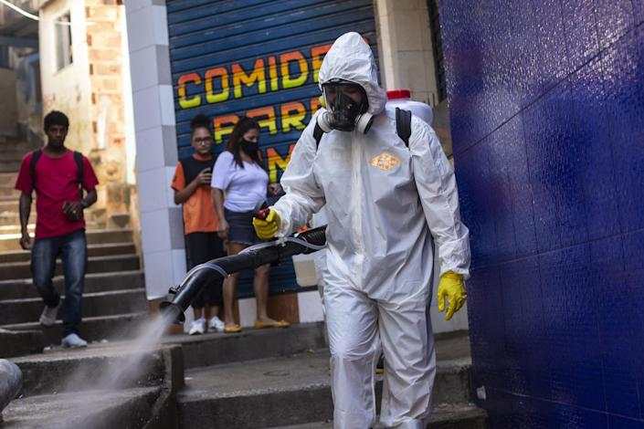 A volunteer sprays disinfectant in an alley.