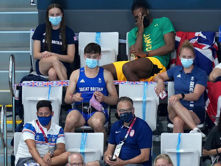 Tom Daley sits in the spectator stands at the Tokyo Olympics and knits amid the women's springboard diving final.