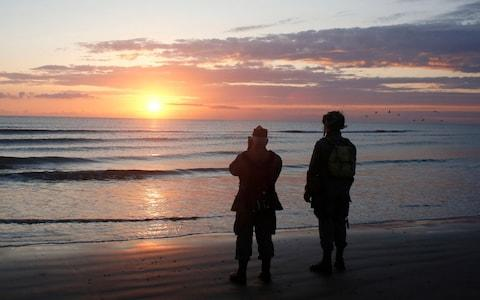 World War II reenactors stand looking out to sea on Omaha Beach, in Normandy, France, at dawn - Credit: AP