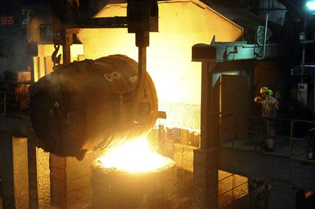 File photo of workers looking at a ladle pouring molten iron into a container at a steel plant in Hangzhou