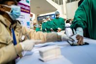 Medical workers wait to be inoculated at a hospital in New Delhi