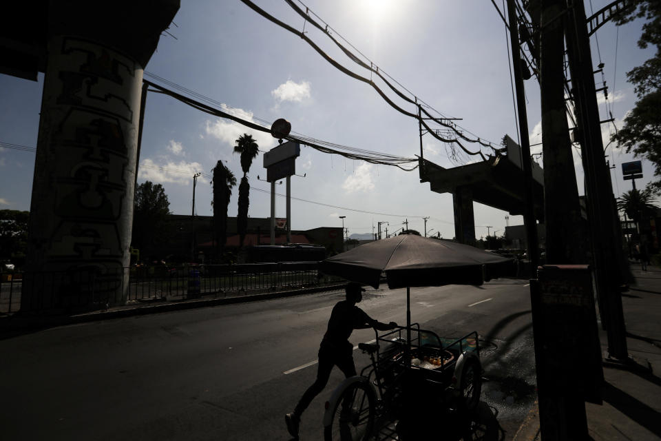 A vendor pushes his bicycle past the missing section of an elevated metro in Mexico City, Wednesday, June 16, 2021. A June 16, 2021, preliminary report by experts into the collapse that killed 26 people placed much of the blame on poor welds in studs that joined steel support beams to a concrete layer supporting the trackbed. (AP Photo/Fernando Llano)