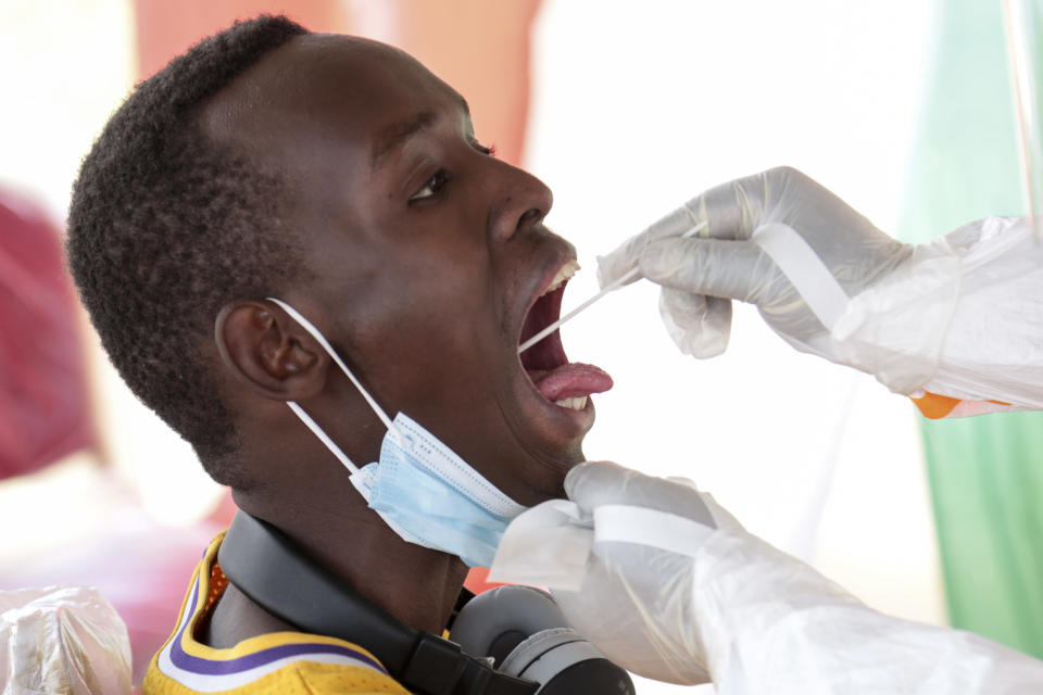 A member of the public is tested for the coronavirus in Bujumbura, Burundi Monday, July 6, 2020. Burundi launched a campaign of mass screening for COVID-19 on Monday in the country's largest city Bujumbura, indicating that the new president Evariste Ndayishimiye is implementing policies to combat the spread of the disease. (AP Photo/Berthier Mugiraneza)