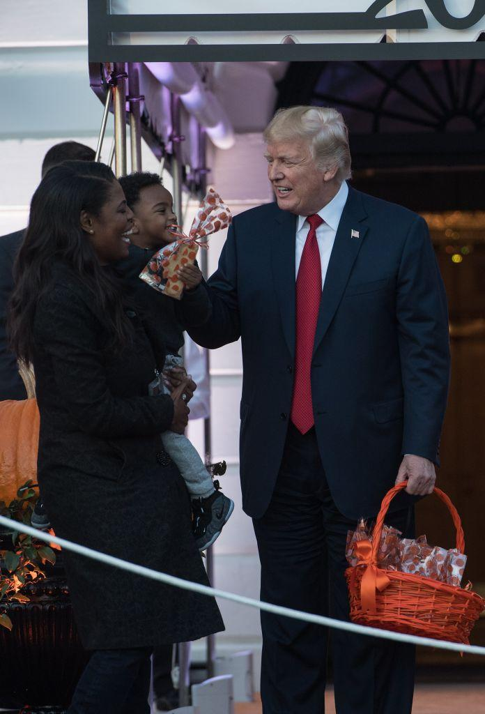 US President Donald Trump speaks with aide Omarosa Manigault as he hands out candy to children during a Halloween event. Source: Getty