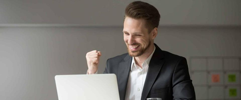 Happy young businessman in suit looking at laptop excited