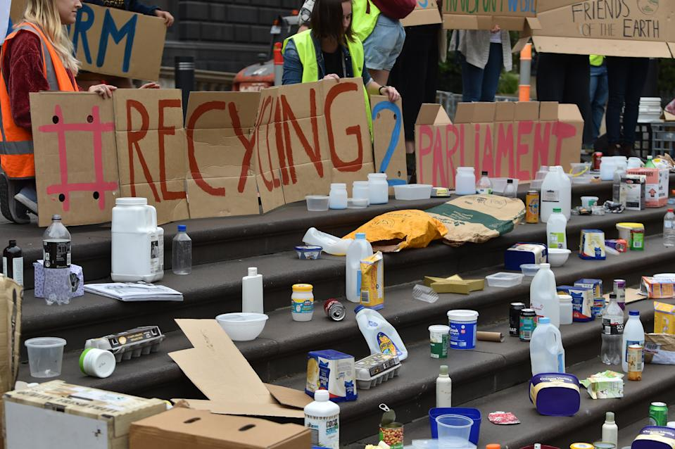 Protesters hold signs in front of plastic bottles and household recycling waste.