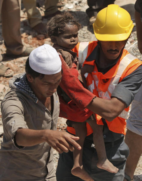 Indian rescue workers carry a young child who survived a building collapse on the outskirts of Mumbai, India, Friday, April 5, 2013. The half-finished building that was being constructed illegally in a suburb of India's financial capital collapsed on Thursday, killing 35 people and injuring more than 50 others, police said Friday. (AP Photo)