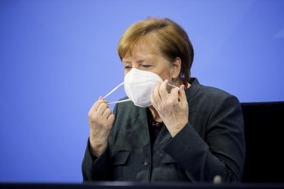 German Chancellor Angela Merkel takes off a face mask as she attends a news conference on further coronavirus measures, at the Chancellery in Berlin, Germany, Tuesday Jan. 19, 2021. (Hannibal Hanschke/Pool via AP)