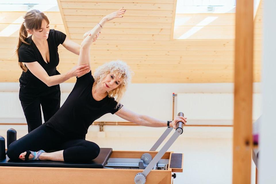 Pilates lesson on reformer, personal coach in black sportswear workout with sporty eldery beautiful blond woman. Rehabilitation and healty lifestyle concept.