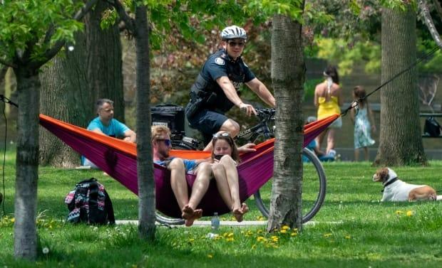A bicycle police officer patrols Trinity Bellwoods Park in Toronto last summer. Warm weather has some questioning what activities can be done outdoors safely.  (Frank Gunn/Canadian Press - image credit)