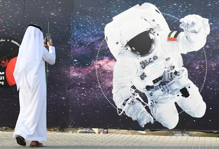 In this file photo from September 2019 a man takes a picture of an illustration of an astronaut with the Emirati national flag outside Dubai's Mohammed Bin Rashid Space Centre (AFP Photo/KARIM SAHIB)