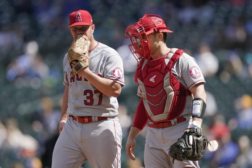 Los Angeles Angels starting pitcher Dylan Bundy, left, talks with catcher Max Stassi on the mound during the fourth inning of a baseball game against the Seattle Mariners, Sunday, May 2, 2021, in Seattle. (AP Photo/Ted S. Warren)