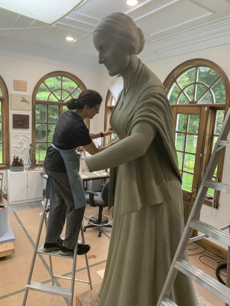In this Sept. 10, 2019 photo provide by Michael Bergmann, artist Meredith Bergmann works on a sculpture of Susan B. Anthony at her studio in Ridgefield, Conn. A New York City commission voted Monday, Oct. 21 to erect a tribute to three civil rights pioneers: Susan B. Anthony, Elizabeth Cady Stanton and Sojourner Truth. Bergmann's work is to be dedicated next August in Central Park, marking the 100th anniversary of women's suffrage in the United States. (Michael Bergmann via AP)