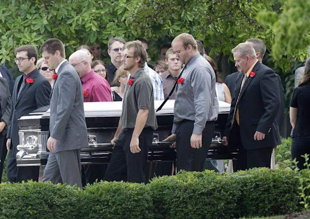 "Pallbearers carry Matt McQuinn, killed in the Aurora, Colorado movie theater shooting, from the church after his funeral Saturday, July 28, 2012, in Springfield, Ohio. McQuinn shielded his girlfriend, Samantha Yowler, from gunfire during the shooting. Twelve people were killed and dozens were wounded in a shooting attack last Friday at a packed movie theater during a showing of the Batman movie, ""The Dark Knight Rises."" Police have identified the suspected shooter as James Holmes, 24. (AP Photo/Jay LaPrete)"