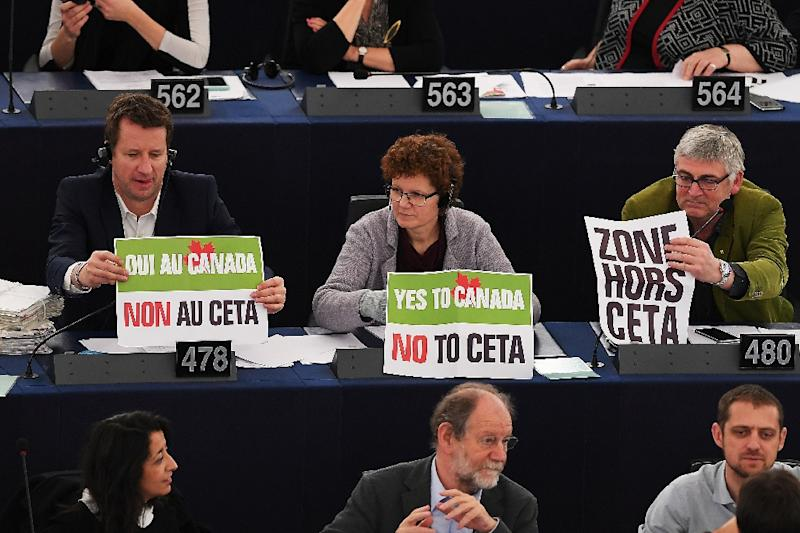 """French Green Party Europe-Ecologie-Les Verts candidate for the 2017 presidential election and MEP Yannick Jadot (L) and other members of the European Parliament hold signs reading, """"Yes to Canada, No to CETA"""" on February 15, 2017 (AFP Photo/FREDERICK FLORIN)"""