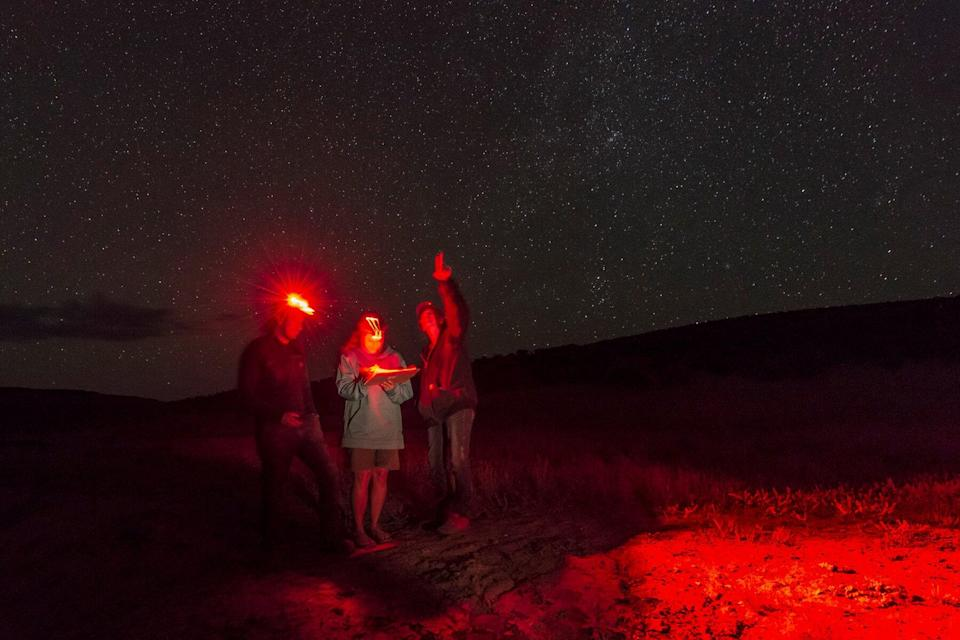 A group of people with headlamps in the Dark Sky Sanctuary in Massacre Rim, Near Reno Tahoe