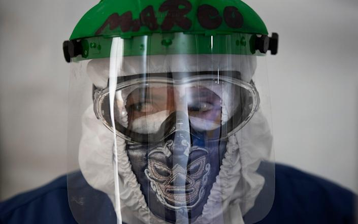 Healthcare worker Marco Antonio Galicia wears a protective face mask designed with a Mexican wrestler motif, in a ward designated for Covid-19 patients, at the Ajusco Medio General Hospital in Mexico City - AP