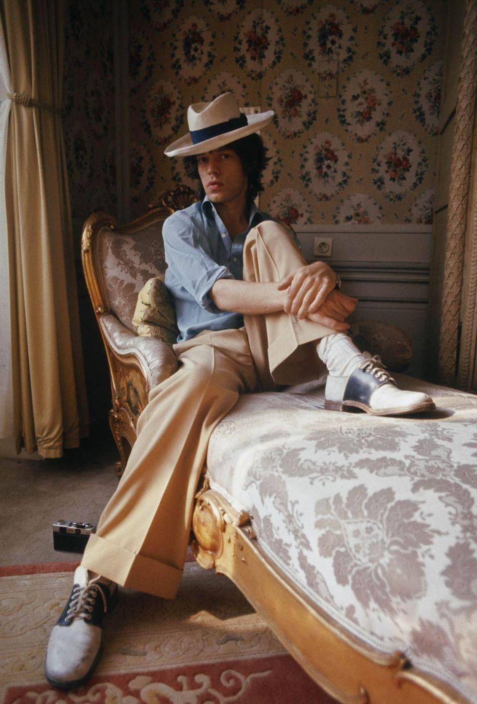 <p>Mick Jagger of the Rolling Stones sitting on a chaise longue in a panama hat and two-tone shoes, October 1973.</p>
